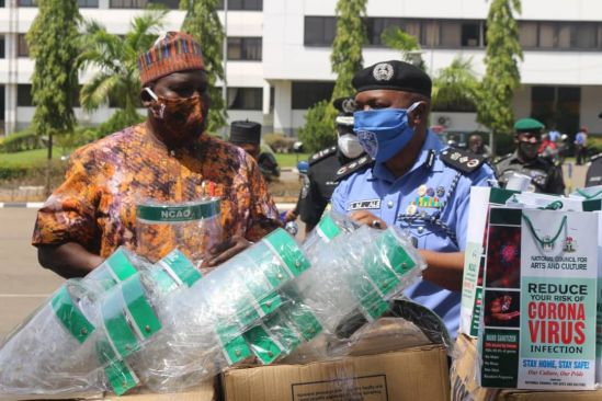L - R: Otunba Olusegun Runsewe DG NCAC presenting locally made Face Shield, Facemasks made of adire, Hand Sanitizers and others to DIG Abdulmajid Ali, DIG Operations (representative of IGP Muhammed Abubakar Adamu mni)
